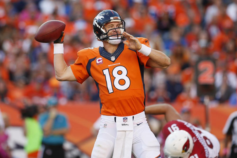 FILE - In this Oct. 5, 2014, file photo, Denver Broncos quarterback Peyton Manning (18) throws against the Arizona Cardinals during the second half of an NFL football game, in Denver. The Broncos won 41-20. Brett Favre says he couldn't be happier to see Peyton Manning on the brink of breaking his own NFL record of 508 touchdown throws. Manning has 503 heading into Denver's road game Sunday Oct. 12 against the New York Jets. (AP Photo/Joe Mahoney, File) ORG XMIT: COJM301